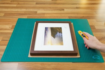 An image showing the Kraft paper being cut to the right size for the frame from John Dunne Photography